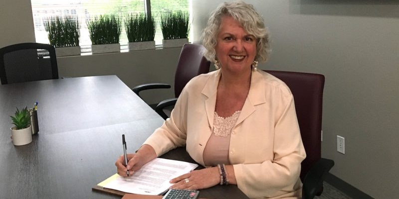 Attorney Theresa Beran Kulat sitting at conference room table in our new offices in Oakbrook Terrace