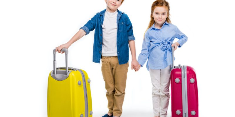 Young brother and sister holding hands while standing with suitcases